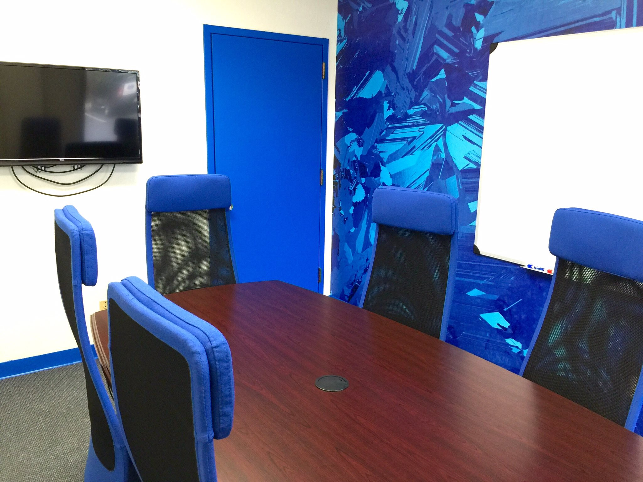 Accent wall in meeting room was given the same Silicon Joule graphic pattern as lobby to tie the two spaces together. Door also painted Gridtential blue.