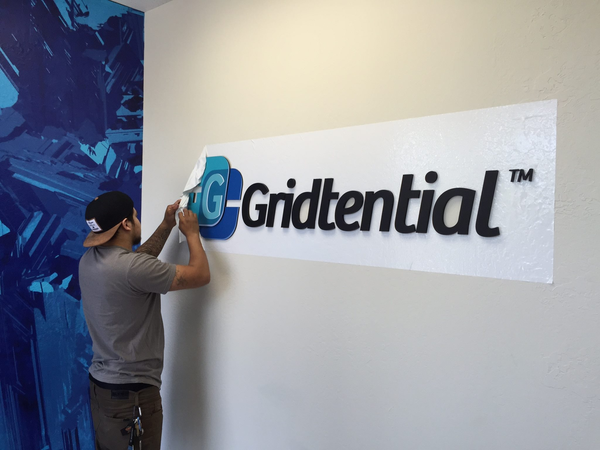 Mounting the 3-D plexiglass Gridtential logo signature on the wall in the lobby.