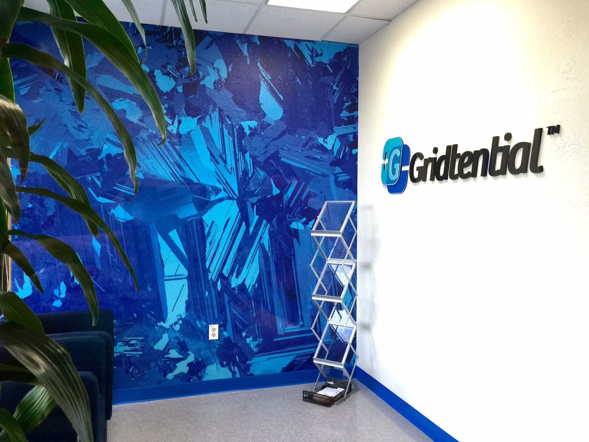 Finished accent wall with bold logo branding for Gridtential.